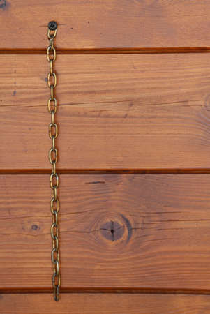 wooden background with vertical metal chain and space to write something