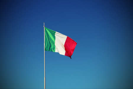 isolated Italian flag waving with blue sky with vignette effect