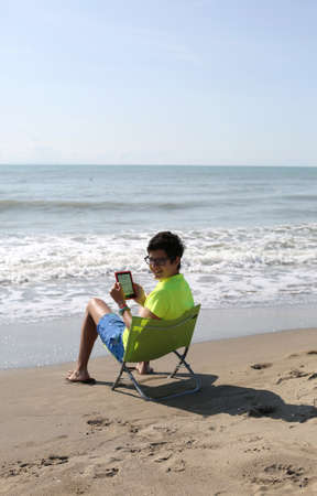 smiling caucasian boy reads a technological e-book on the beachside seashore in summer Stock Photo
