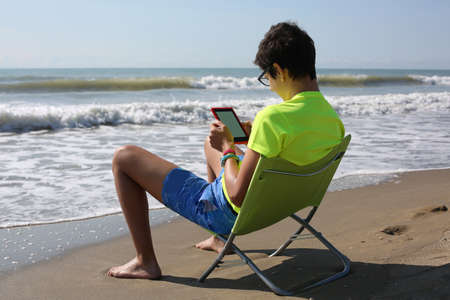 young boy reads an ebook at the seaside during summer vacation