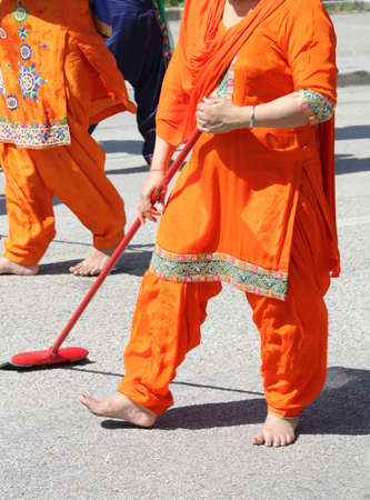 Sikh religion woman during the ceremony along the streets of the city while sweeping the streets with the broom