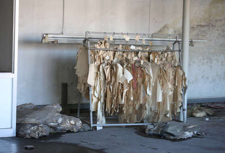 abandoned clothing manufacturing factory with the ruined sample hanging on the cloakroom