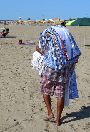 african abusive street vendor with towels and fabrics on the beach