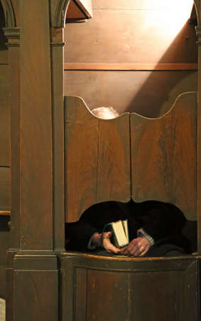 old priest inside the confessional in a Christian church waiting for the faithful to confess Imagens