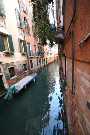 very narrow navigable canal in Venice in Italy with boat