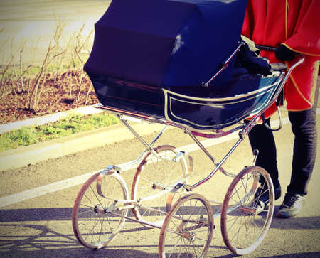 Ancient baby carriage pushed by a person with lomo effect