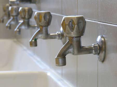 serie di molti rubinetti in bagno nella scuola elementare