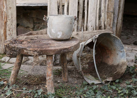 tin bucket and an aluminum pot over the stool of the old abandoned stable
