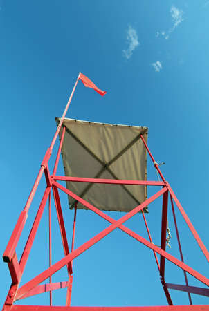 big turret of lifeguard on the beach with the red flag to signal the danger