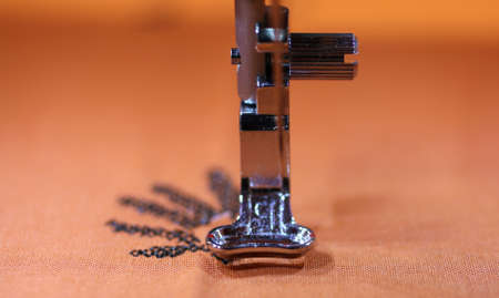 needle laces: movement of the sewing machine with a steel needle and the embroidery on the fabric Stock Photo