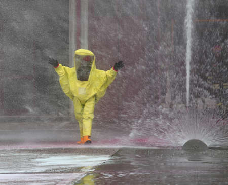 man with yellow protective suit and splashes of water to cool the surrounding environment Reklamní fotografie