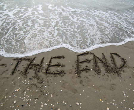 THE END text written on the sand and the wave that is deleting the word can be used for the purpose of corporate presentations