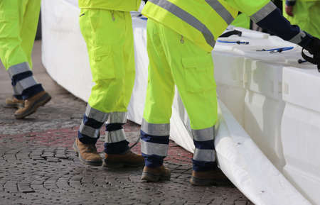 civil protection men with high visibility clothing during an exercise to prevent flooding in the city Imagens