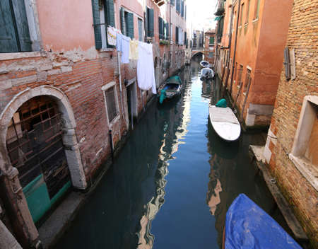 very narrow navigable canal in Venice in Italy with boats and italian houses Stock Photo - 89353952