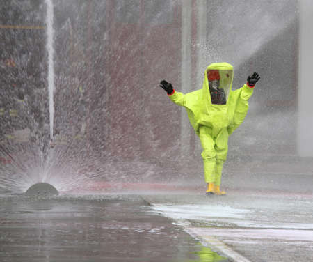 man with yellow protective suit and splashes of water to decontaminate the surrounding environment