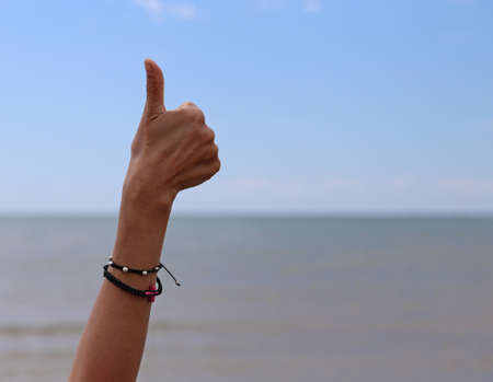girls hand with thumb up that means its all right and sea in background