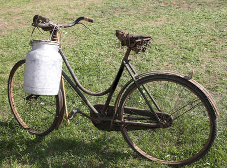 Antique milk can aluminum used once a long time ago from the milkman to deliver the beverage to the dairy by an old bike