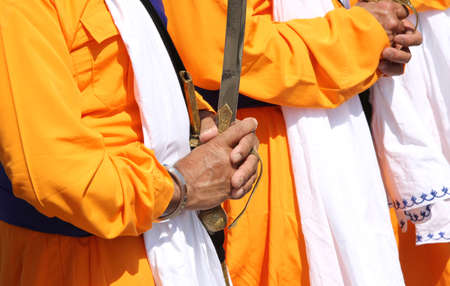 group of people with orange dresses during the religious sikh event with the long sword in hand Stock Photo