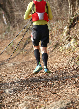 sporty runner during walking with sticks called nordic walking Фото со стока