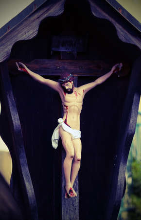 Ancient wooden statue depicting crucified Jesuit with vintage effect Stock Photo