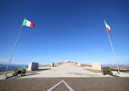 ample: Vicenza, VI, Italy - December 8, 2015: War Memorial of First War World called Ossario del Monte Grappa. Main avenue with two italian flags and old cannons