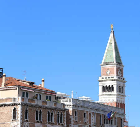 tip of San Marco bell tower behind the roofs of the houses