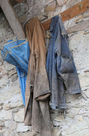 old clothes of a farmer hanging in a rural house