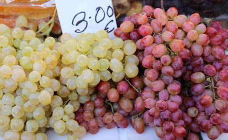 red and white grapes for sale at fruit market in autumn