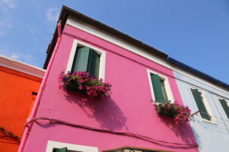 detail of pink house with flowery balcony in the town of Burano