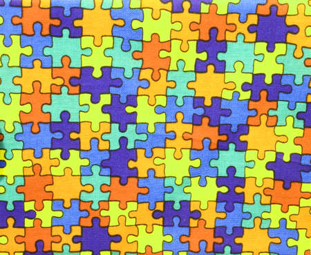 background of many pieces of colored puzzle on dyed cotton fabric Stock Photo