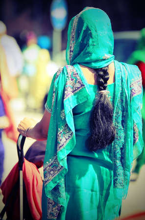 scarves: young woman with decorated dress and long black hair braid coming out of the veil while pushing a stroller to the city