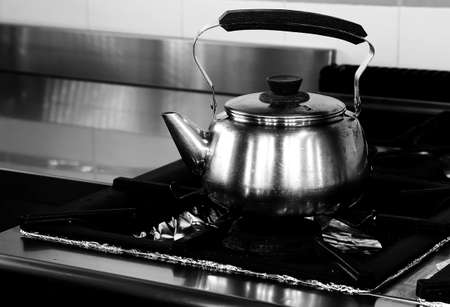 large steel teapot above the restaurants industrial cooker with black and white effect