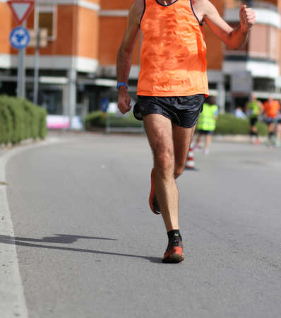 legs of runner while he runs at marathon race in the city Imagens