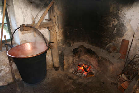 cauldron to heat whey for cheese production in a dairy inside the stall in the mountain