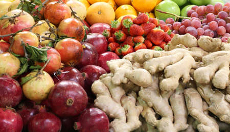 background of many fresh fruit and in the greengrocer pomegranate ginger root and apples strawberries grape oranges