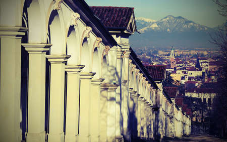 long row af arched arcades and city of VICENZA in background and vintage effect