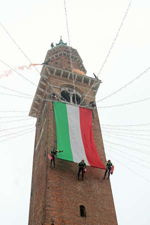 Vicenza, VI, Italy - December 4, 2015: Firefighters with a big italian flag and the tower of ancient Palace called Basilica Palladiana during an exercise