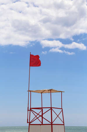 Lifeguard tower with red flag in tropical resort beach