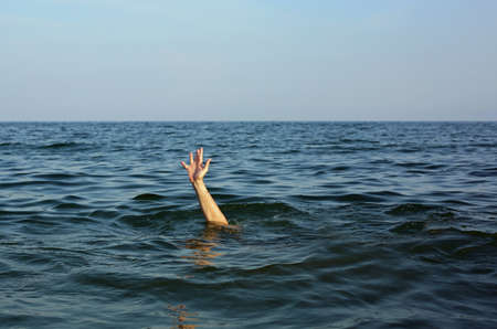 hand of the man while asking for help drowning in the sea Foto de archivo