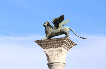 lion wings of St. Mark on a marble pedestal with a blue sky