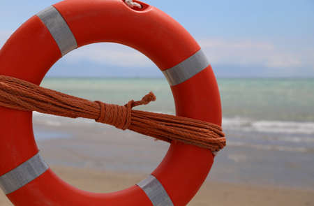 huge orange life-buoy by the sea with the rescue rope