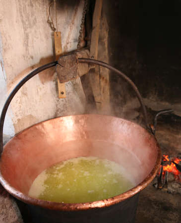 big cauldron with whey for cheese production in a dairy inside the stall in the mountain Stock Photo