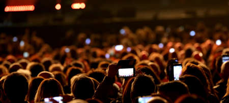 many young people with smart phones at live concert