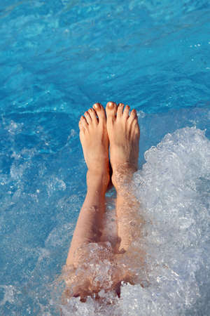 barefoot feet of the young woman during a hydromassage session in the luxurious spa
