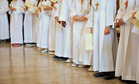 children with white tunic during the religious rite of the First Eucharistic communion