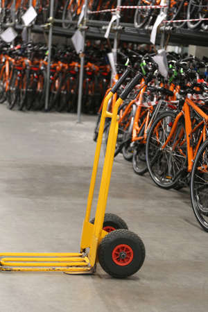 wide storage room with many bicycles and a yellow manual carrying carriage Stock Photo