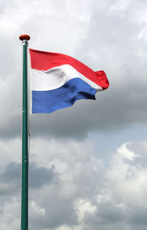 very large Dutch flag waving with cloudy sky