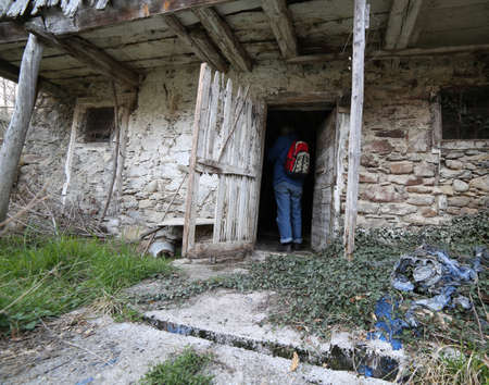 Young  backpacker enters the old abandoned stable in northern Italy at the resort called CARNIA near the border with Austria
