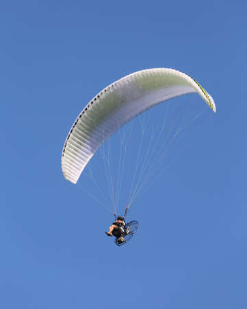 big Motor powered hang glider flies high in the blue sky with a person sitting as a pilot Stock Photo
