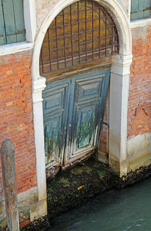 rotten broken wooden gate on a canal of the island of Venice in Italy